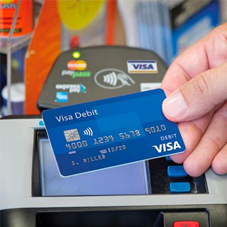 Person holding a Visa credit card in front of a payment terminal displaying the contactless symbol and credit card logos.