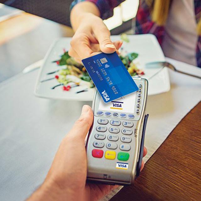 Contactless Visa card being used at a QSR